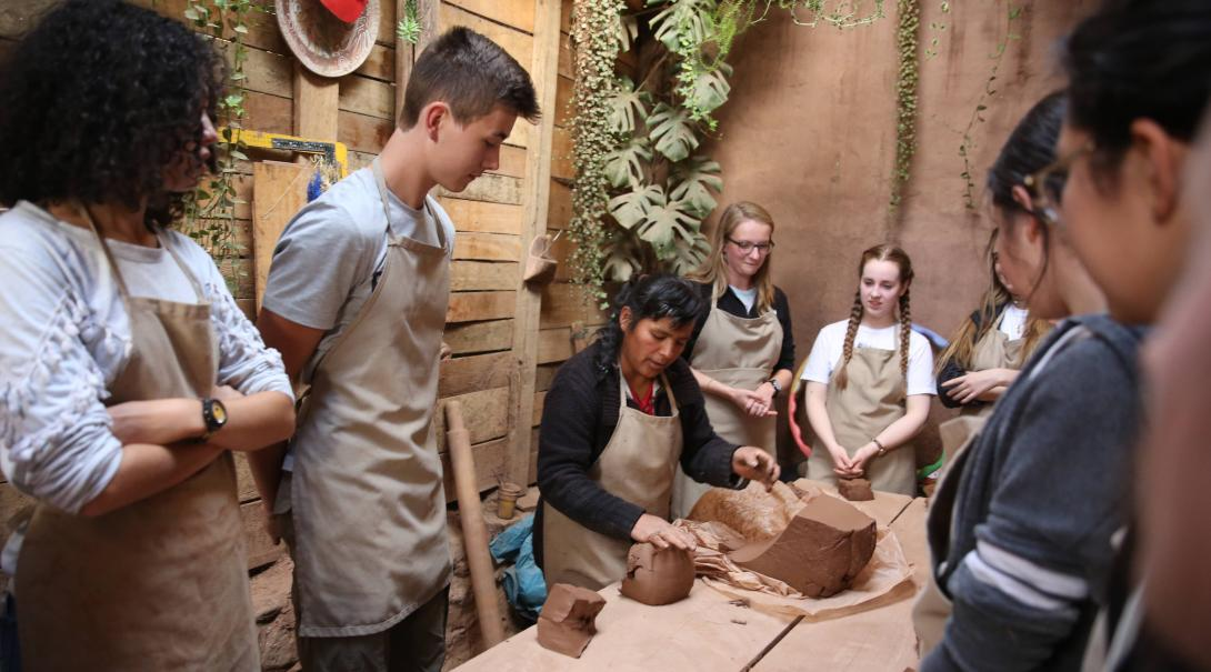 Volunteers learn about clay during a workshop as part of their community volunteer work in Peru for teenagers.